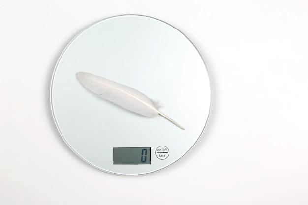 Witte vogelveer wordt gewogen op een digitale weegschaal