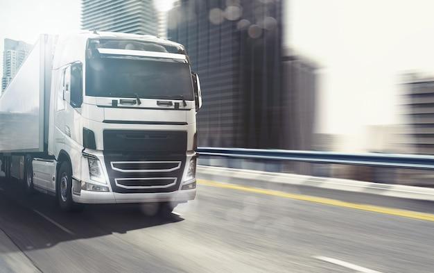 Witte vrachtwagen beweegt snel op de snelweg met een moderne stad