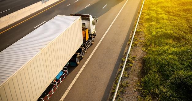 Witte vrachtwagen op snelweg weg met container, transport concept., import, export logistieke industriële transporteren landvervoer op de expressway.motion wazig tot zachte focus