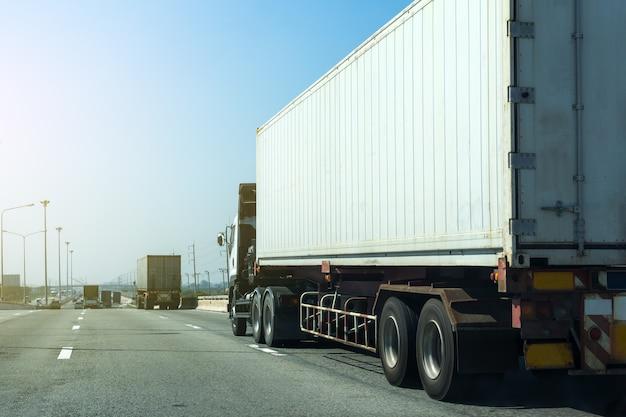 Witte vrachtwagen op wegweg met container, logistisch industrieel vervoer