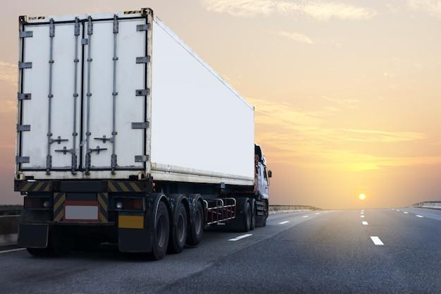 Witte vrachtwagen op wegweg met container, vervoer op de asfaltuitgang