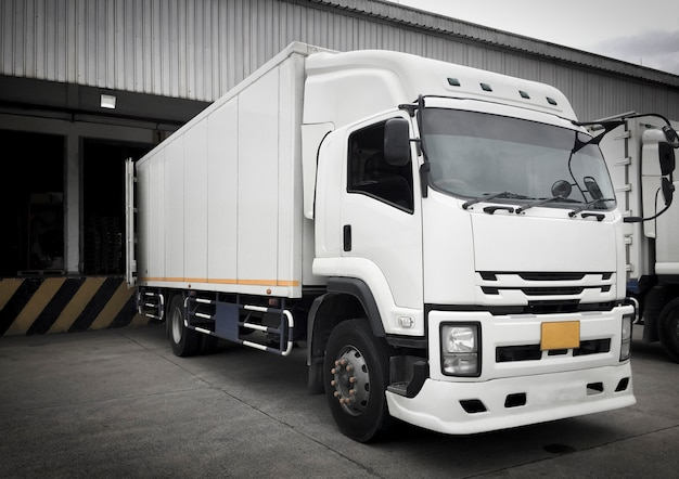 Witte vrachtwagens die ladingslading dokken bij distributiemagazijn