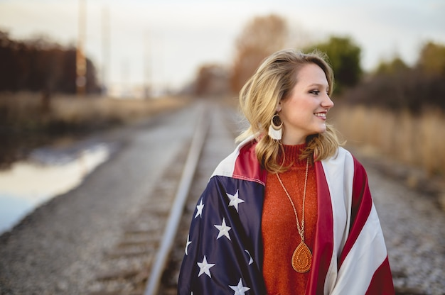 Witte vrouw bedekt met de vlag van de verenigde staten van amerika