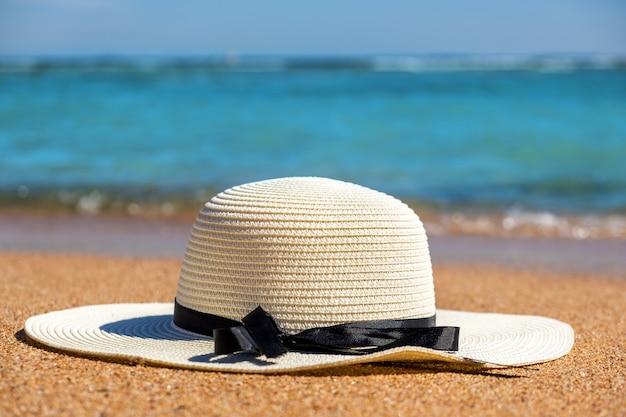 Witte vrouw strooien hoed opleggen op tropisch zandstrand met blauwe levendige oceaanwater op achtergrond op zonnige zomerdag. vakanties en reisbestemming concept.