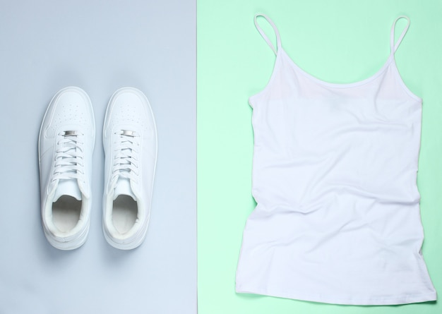 Witte vrouw t-shirt, witte hipster sneakers op pastel achtergrond