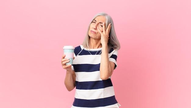 Witte vrouw van middelbare leeftijd die zich verveeld, gefrustreerd en slaperig voelt na een vermoeiende en een afhaalkoffiecontainer vast te houden