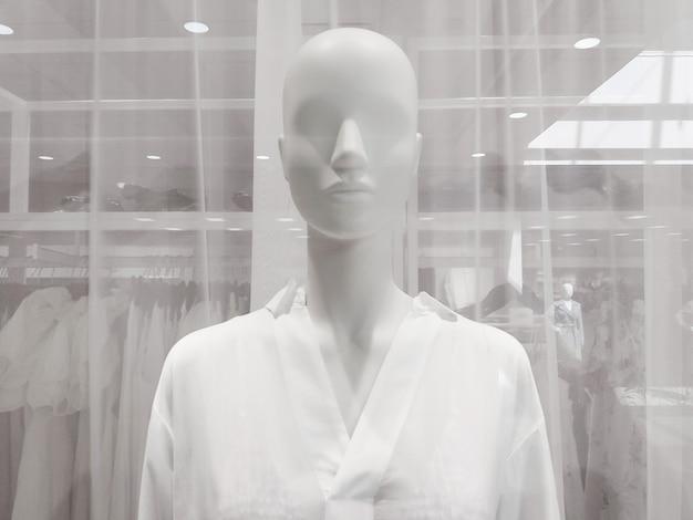 Witte vrouwelijke etalagepop in kledingwinkelraam, close-up