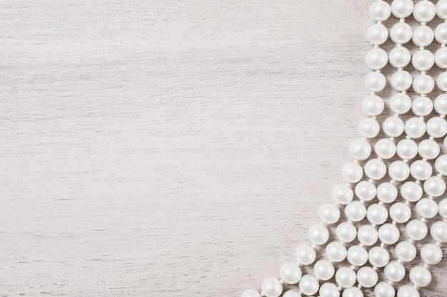 Witte vrouwelijke parels op witte houten achtergrond, vrouwelijke sieraden op een witte houten tafel