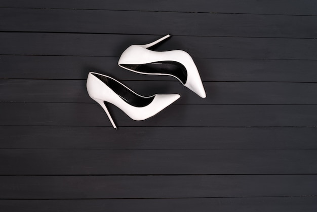 Witte vrouwelijke schoenen op een zwarte houten ondergrond