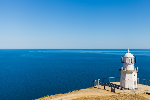Witte vuurtoren op een achtergrond van blauwe zee
