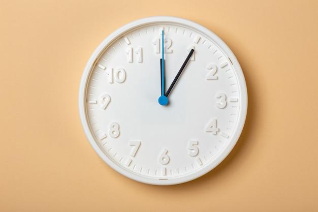 Witte wandklok met blauwe secondewijzer geeft één uur aan