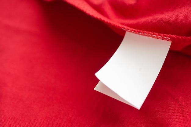 Witte wasverzorging wasinstructies kledinglabel op rood katoenen overhemd
