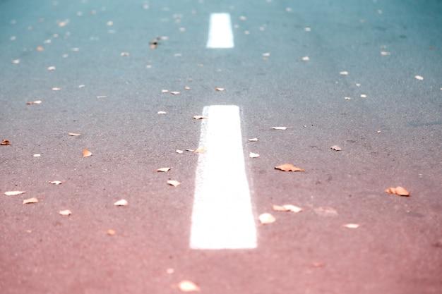 Witte wegstrook die op asfalt merkt.