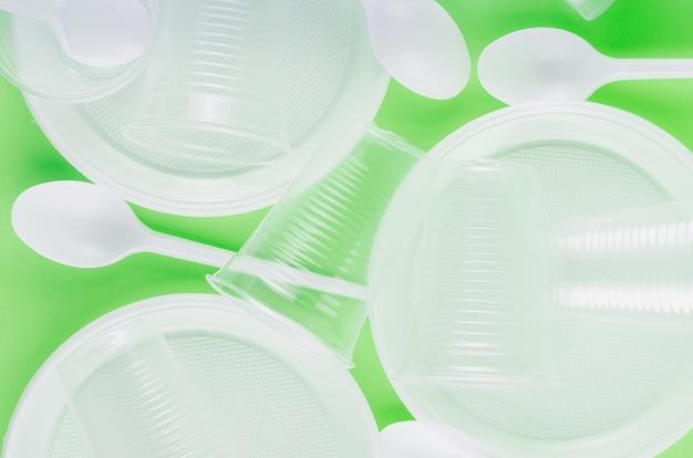 Witte wegwerpbekers, borden, vorken, messen op lichtgroene close-up als achtergrond