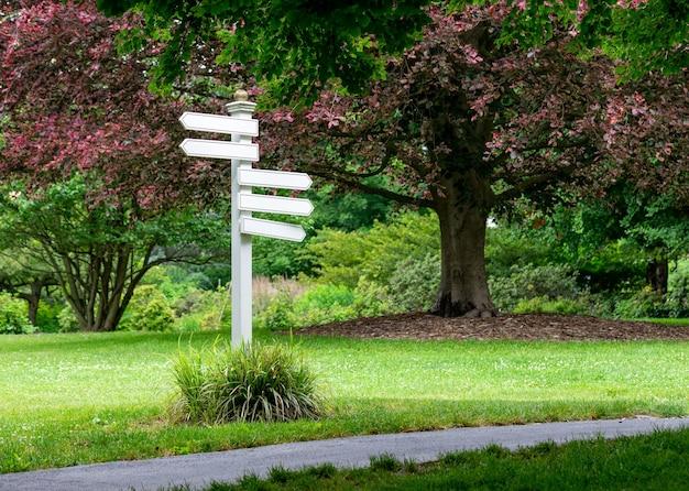 Witte wegwijzer met lege richtingborden erop die in verschillende richtingen wijzen