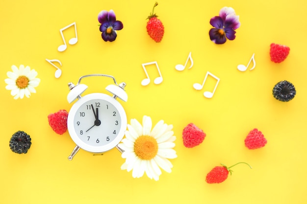 Witte wekker, bloemen, bessen en notities op een gele achtergrond. ruimte kopiëren.