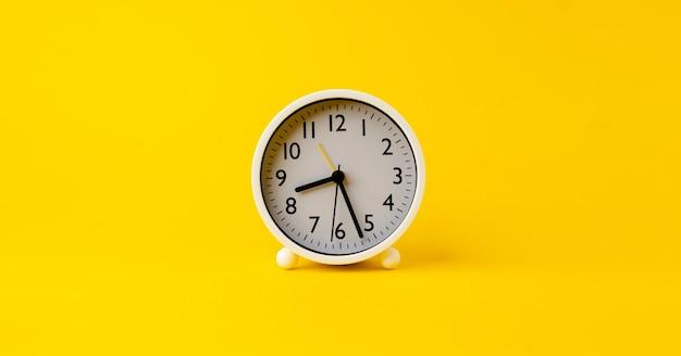 Witte wekker de klok vertelt de tijd om 's ochtends wakker te worden. geplaatst op een gele achtergrond