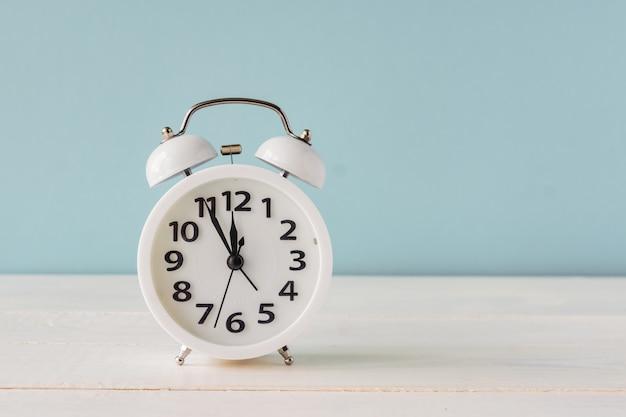 Witte wekker die zich op houten plank op blauwe achtergrond bevindt. kopieer ruimte voor uw tekst of ontwerp. minuten voor twaalf op een display