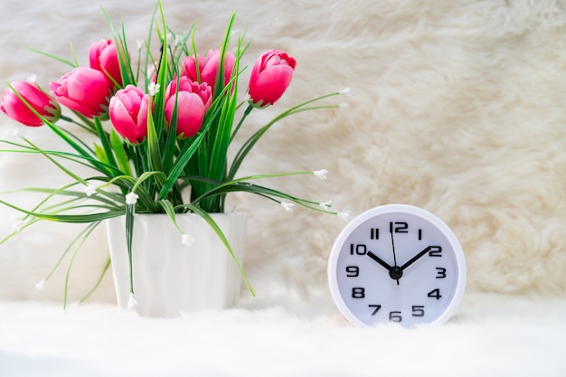 Witte wekker en bloem in vaas op tafel