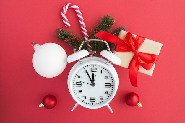 Witte wekker en kerstmissamenstelling op het rode oppervlak
