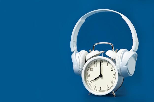 Witte wekker en koptelefoon op een blauwe achtergrond. muziek. rust uit. plaats voor tekst.