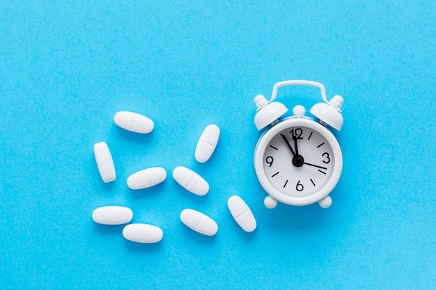 Witte wekker en witte ovale pillen ernaast op een blauwe achtergrond