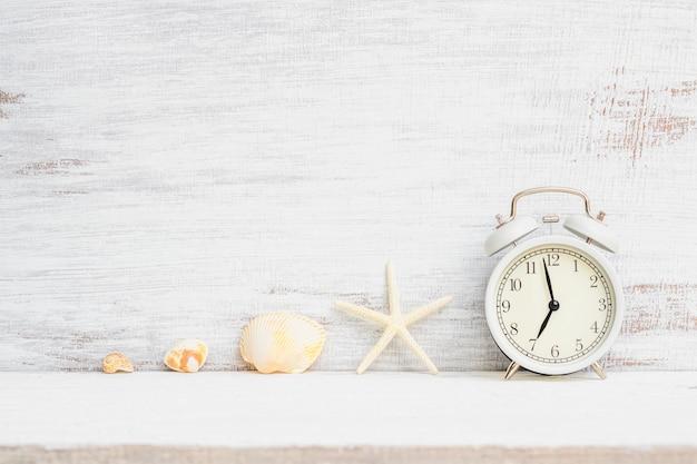Witte wekker met zeester, zeeschelpen op witte roestige houten achtergrond. achtergrond concept voor zomervakantie vakantievakantie, zee strand reizen vakantietijd.