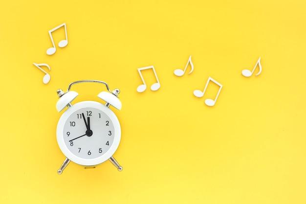 Witte wekker op een gele achtergrond en notities rond. ruimte kopiëren. concept.