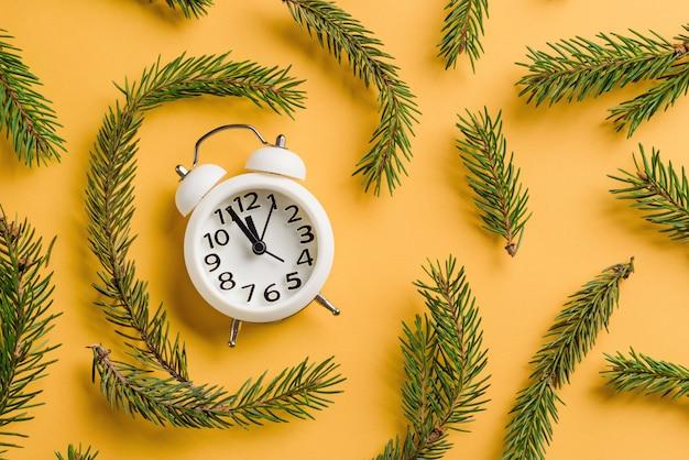 Witte wekker op een gele onder de kerstboomtakken.