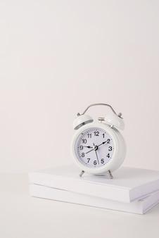 Witte wekker op stapel boekenmodelontwerp