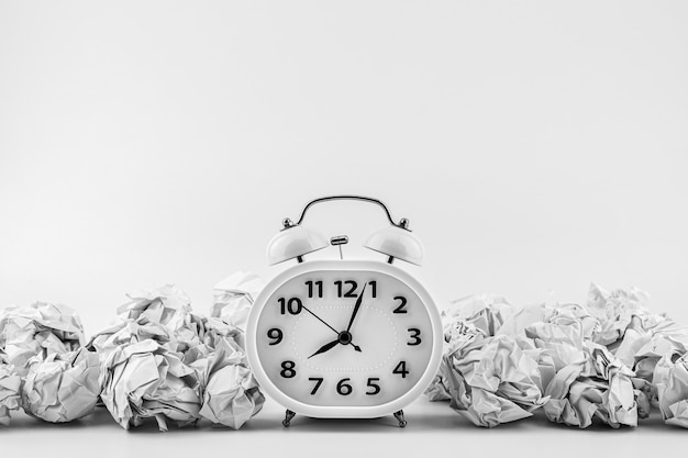 Witte wekker temidden van verfrommelde papieren balpalen. - bedrijfstijden concept.