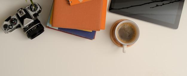 Witte werktafel met kopie ruimte, camera, notebooks, digitale tablet en koffiekopje