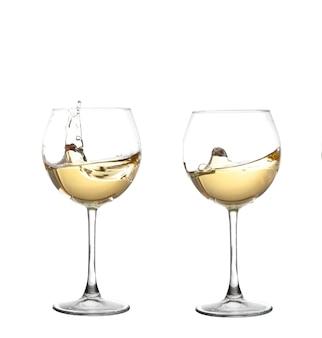 Witte wijn die in een glas van de drinkbekerwijn wervelt, dat op een witte muur wordt geïsoleerd