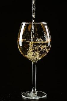 Witte wijn die in een wijnglas op een donkere achtergrond wordt gegoten