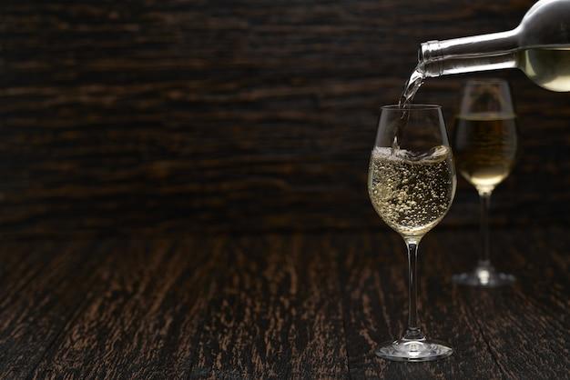 Witte wijn in de glazen gieten tegen houten tafel