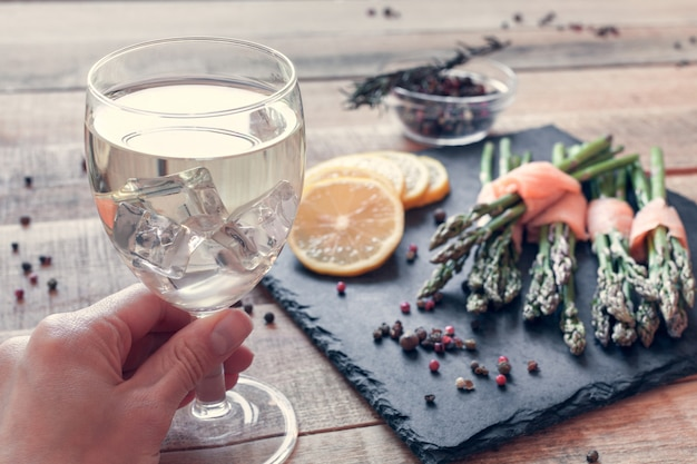 Witte wijn in de hand en bosjes asperges gewikkeld in zalm