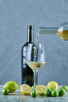 Witte wijn in het glas en citroenen gieten, fles wijn en kersenpruimen apart