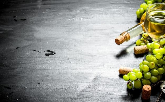 Witte wijn met druiventakken. op een zwarte houten achtergrond.