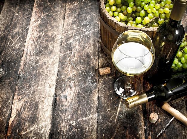 Witte wijn met een emmer groene druiven. op een houten tafel.