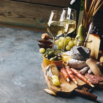 Witte wijn met vleeswarenassortiment op de steenachtergrond
