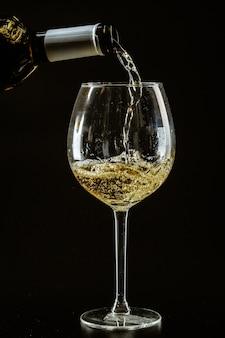 Witte wijn wordt gegoten in een wijnglas
