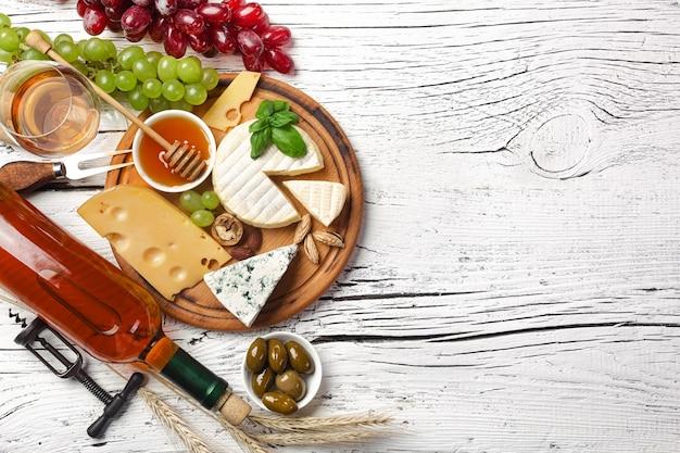 Witte wijnfles, druif, honing, kaas en wijnglas op wit houten bord. bovenaanzicht met kopie ruimte.