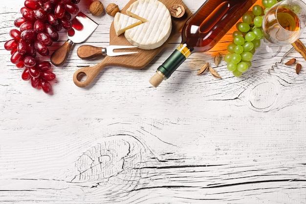 Witte wijnfles, druif, kaas en wijnglas op witte houten bord