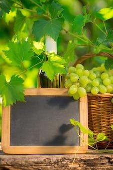 Witte wijnfles, schoolbordspatie en tros druiven tegen groene lenteachtergrond