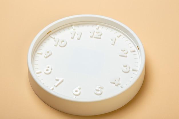 Witte wijzerplaat van wandklok zonder wijzers op een beige achtergrond