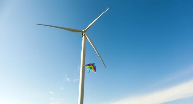 Witte windturbines met vliegers tegen de blauwe hemel