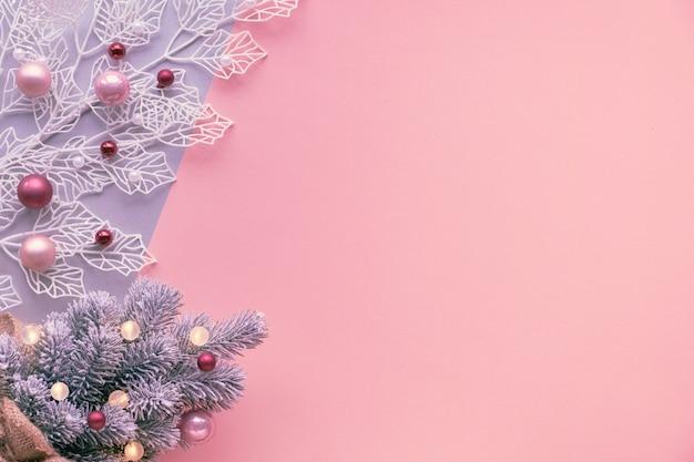 Witte wintertak met glanzende geometrische bladeren en kunstkerstboom versierd met lichtjes en glazen kerstballen. feestelijke kerst plat lag op twee kleuren papier, roze en zilveren muur, kopie-ruimte.