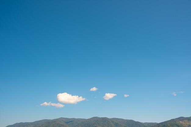 Witte wolken en blauwe lucht boven de berg