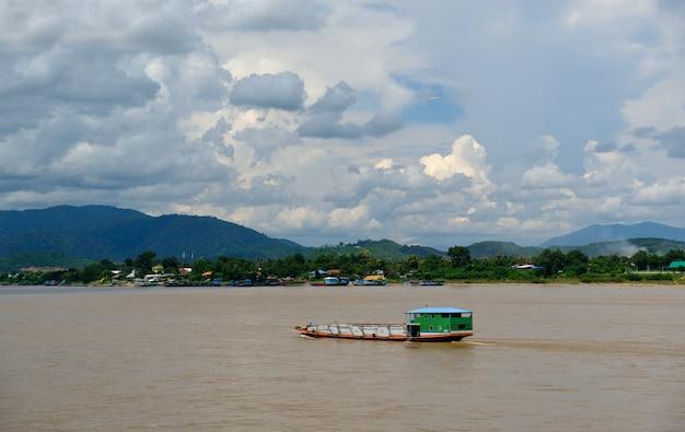 Witte wolken met een blauwe lucht, lange staart boot afgemeerd aan de mekhong rivier