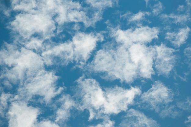 Witte wolken met gescheurde randen over blauwe hemelachtergrond